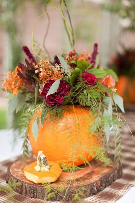 ein Kürbis-vase mit bunten Blumen und viel grün Einordnung als fall-Hochzeits-Mittelstück