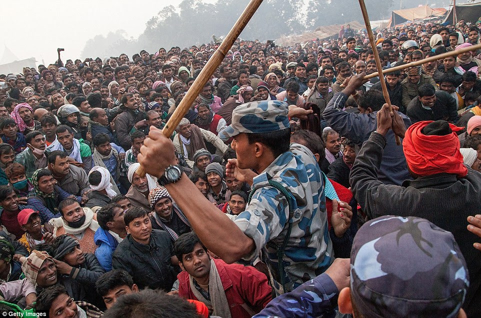 A member of the police force attempts to control the vast crowd. The festival has prompted numerous protests by animal rights activists and Nepalese Hindus from Hill region