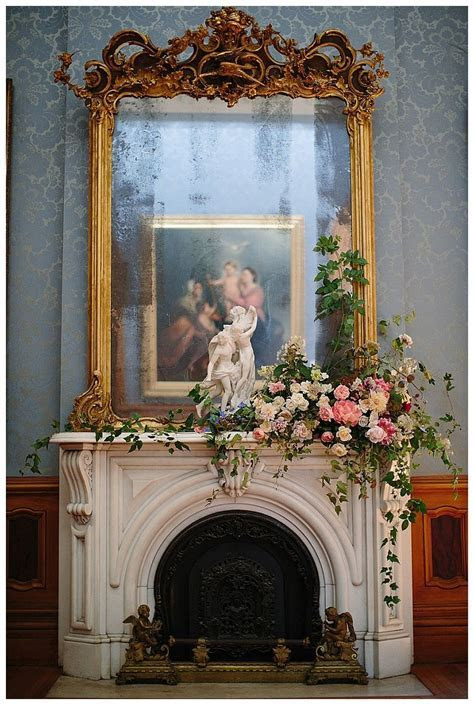 Lush florals and a gilded mirror on the fireplace mantle