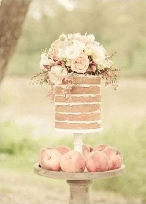 Flower-topped naked cake surrounded by pieces of fruit