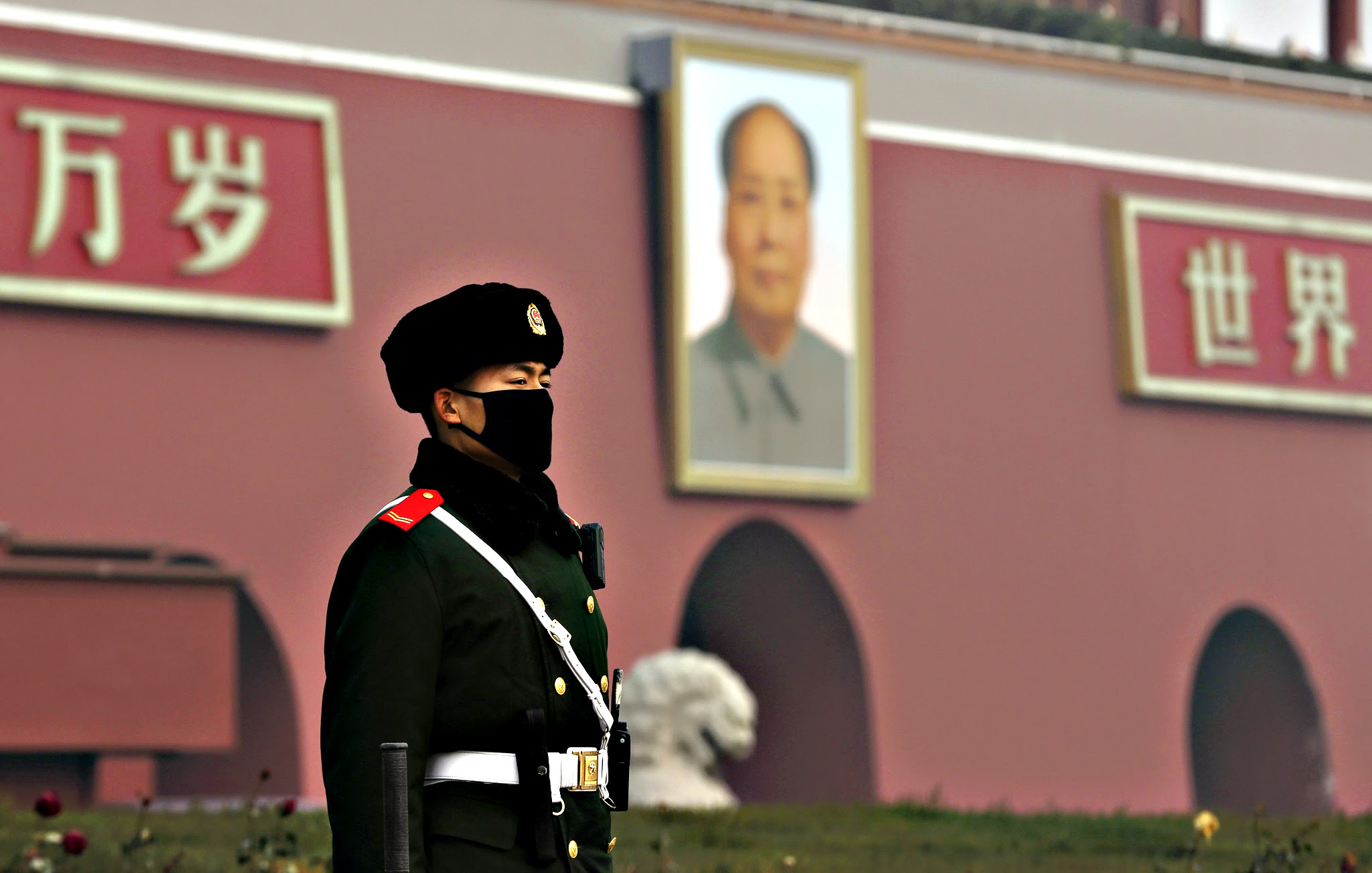 """A paramilitary policeman wearing a mask stands guard in front of the giant portrait of Chinese late chairman Mao Zedong, amid heavy smog after the city issued its first ever """"red alert"""" for air pollution in Beijing, China, December 9, 2015. Picture taken December 9, 2015."""