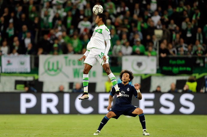 Bruno Henrique salta diante de Marcelo em Wolfsburg x Real Madrid (Foto: AP Photo/Markus Schreiber)