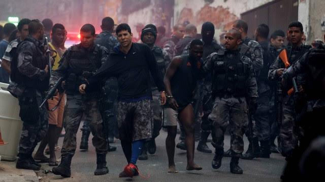 O homem que tentava se esconder, ao centro da imagem, desce o morro Pavão-Pavãozinho escoltado por policiais do Batalhão de Choque