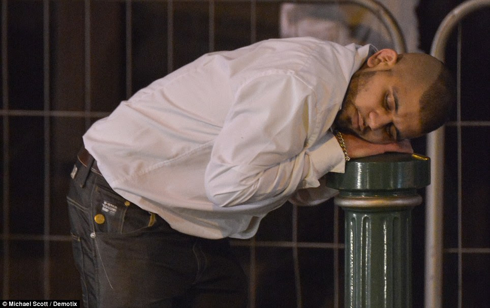 Catching up on some sleep: A New Year's Eve reveller has a well earned rest by placing his head on a bollard in the middle of Broad Street in Birmingham