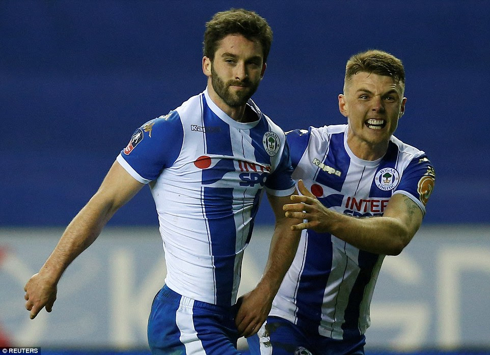 Will Grigg (left) scored a dramatic late winner as Wigan beat Manchester City in the FA Cup fifth round on Monday night