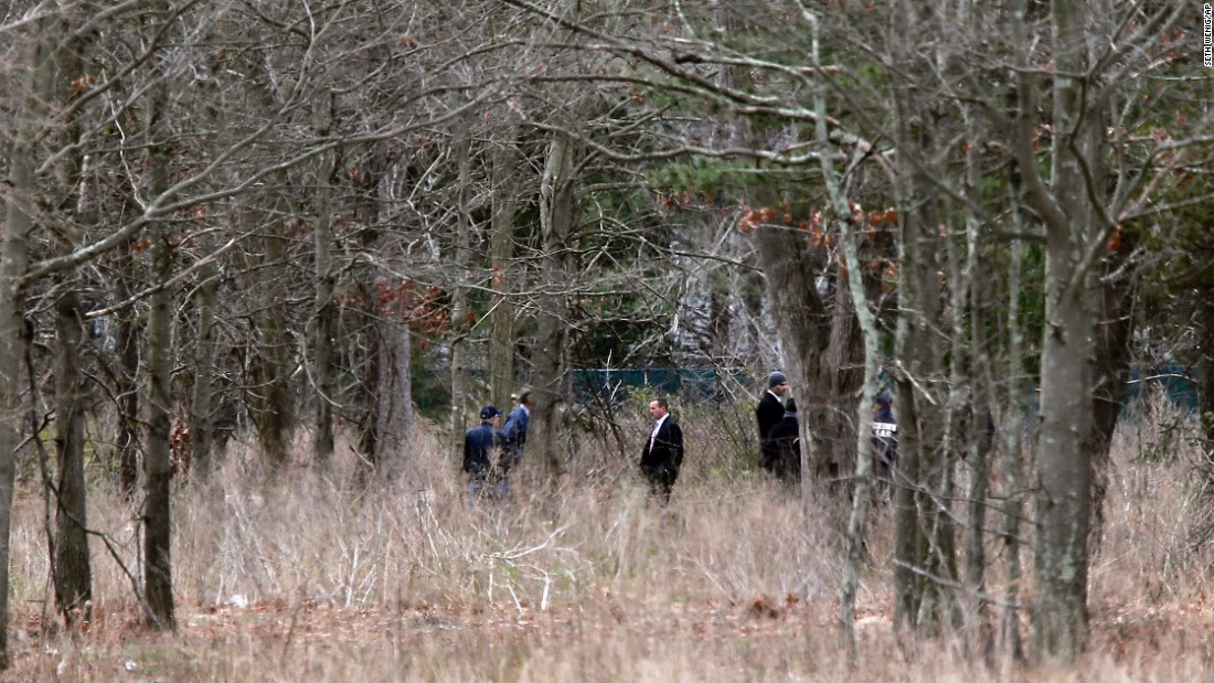 Investigators comb woods where the mutilated bodies of four young men were discovered in late April in Central Islip. Authorities believe MS-13 was behind the killings.