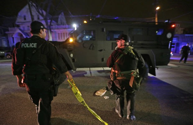 Policiais procuram o segundo suspeito de causar as explosões durante a Maratona de Boston. O primeiro suspeito foi morto (Foto: Julio Cortez/AP)