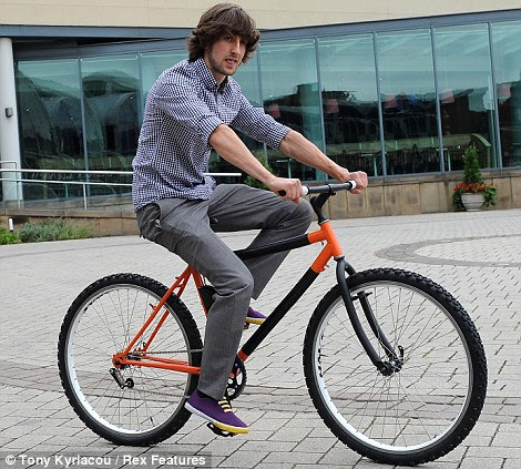 On his bike: Kevin Scott demonstrates that his revolutionary folding design can be ridden like a traditional bicycle
