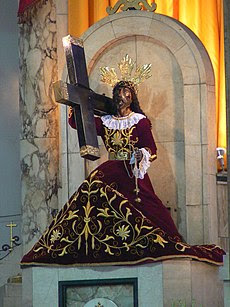 Jesus as the Black Nazarene with red robes and carrying a cross