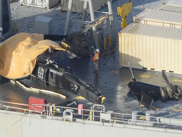 Partes de um helicóptero do Exército dos EUA que sofreu um acidente e caiu no mar perto da ilha de Okinawa, no Japão, foram resgatadas e colocadas no deque do navio USNS Red Cloud. O helicóptero caiu durante missão de treinamento, ferindo 6 pessoas (Foto: Reuters/Kyodo)