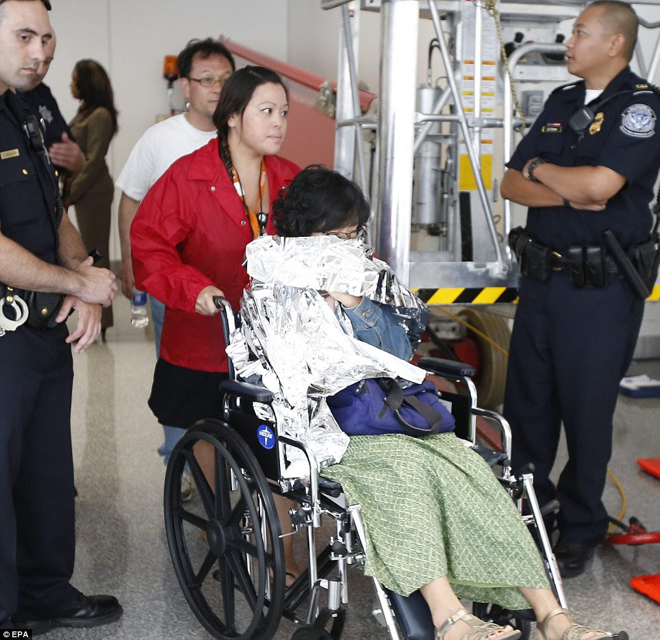 Rescue: A woman is taken away from the airport's reflection room where passengers rested after their ordeal
