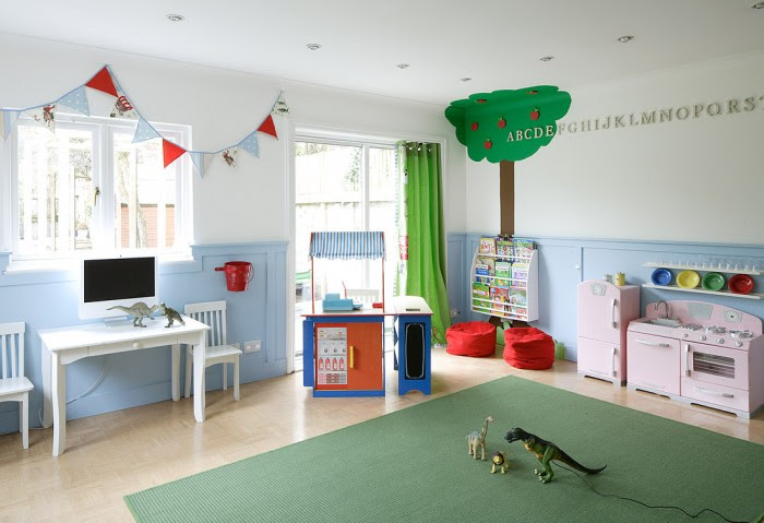 apple tree mural and bunting clad child's playroom in white and baby blue