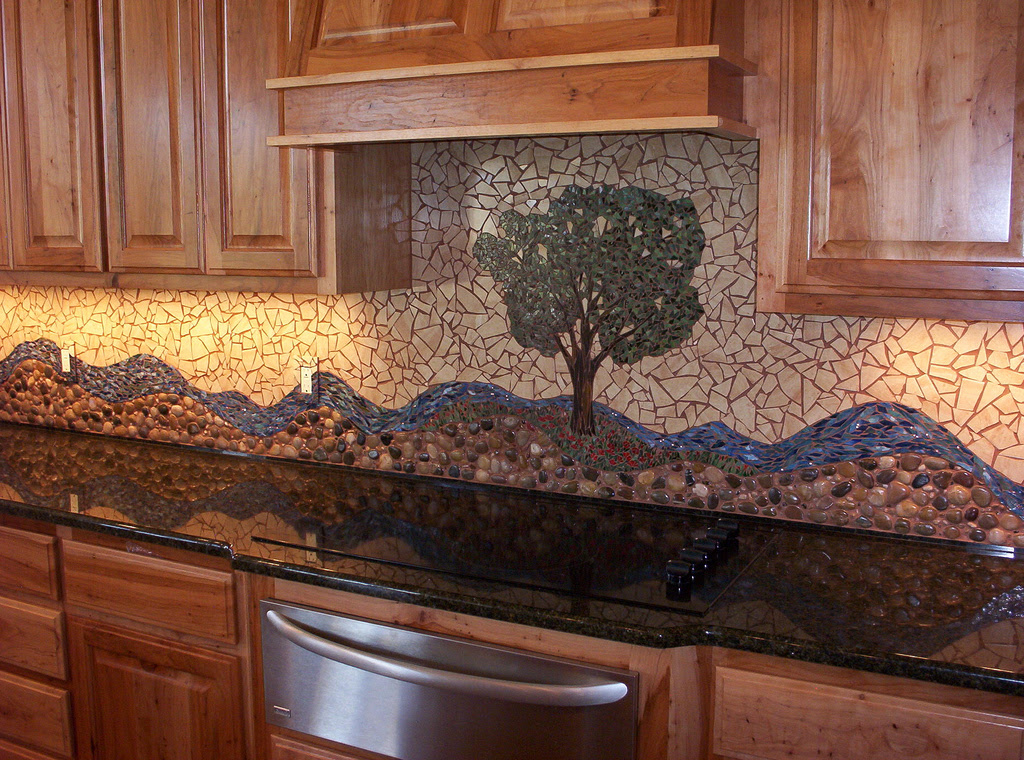 two comined style backsplash tiling between mosaic tiles and river rocks tiles a tree picture backsplash decoration made from mosaic tiles an electric stove as the most modern kitchen appliance