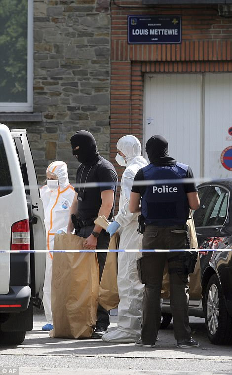 Police and forensic officers remove items during a house search in the Molenbeek district of Brussels on Wednesday
