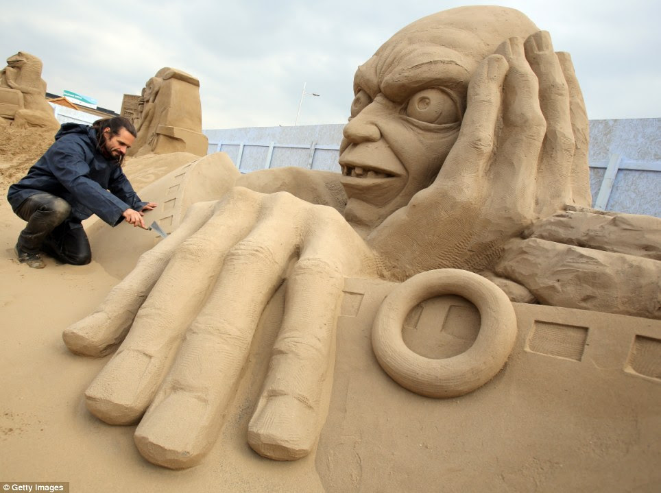 My precioussss: Sand sculptor Radavan Zivny works on a spitting image of Lord of the Rings villain Gollum, in line with this year's Hollywood theme