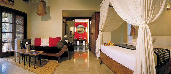 A canopied bed sits as a focal point in an open plan deluxe villa.