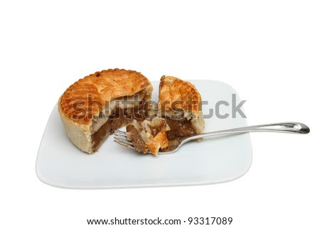 Steak pie with a fork on a plate isolated against white ...