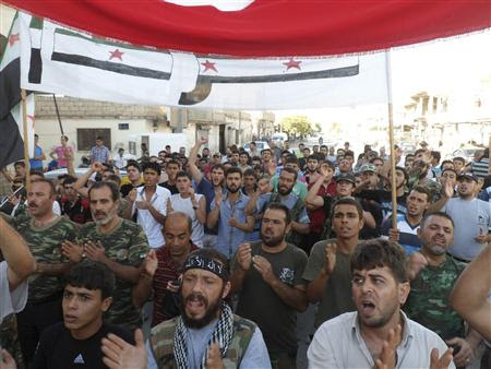 Members of the Free Syrian Army and residents shout slogans during a protest against Syria's President Bashar al-Assad in Sermada near Idlib, September 25, 2012. REUTERS/Shaam News Network/Handout
