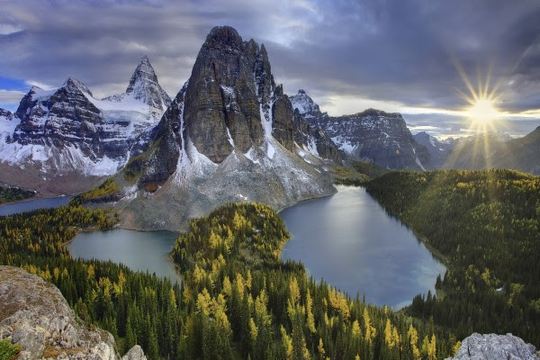 El radiante sol iluminando un bello paisaje de montañas y lagos