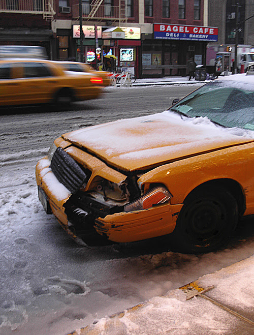 Taxi with broken bumper and snow