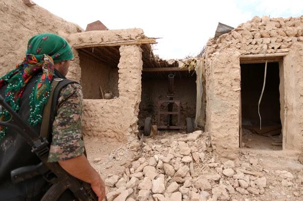 Membro das Forças Democráticas Síria inspeciona área que era ocupada por militantes do Estado Islâmico, em região rural no sul de Manbij (Foto: Rodi Said/Reuters)