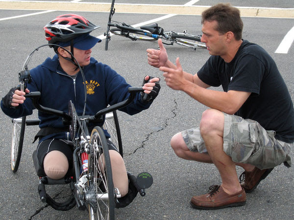 Steve Nardizzi explains the brakes on the handcycle to Elmer Dinglasan, a Navy corpsman participating in the second leg of Soldier Ride 2006, from Washington, D.C., to Camp Lejeune N.C. (Photo by Sgt. Sara Wood)