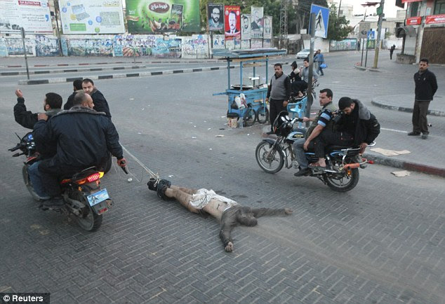 Dragged through the dirt: One of the killed six lays on the floor as shocked bystanders watch on
