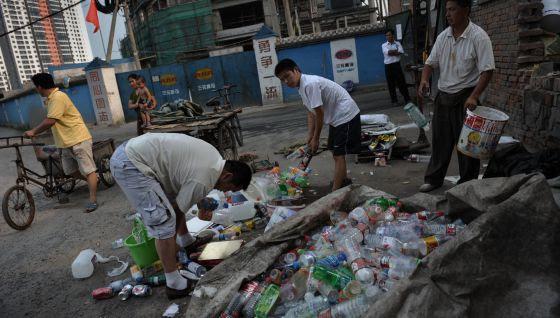 Ciudadanos chinos recogen basura en una calle de Pekín