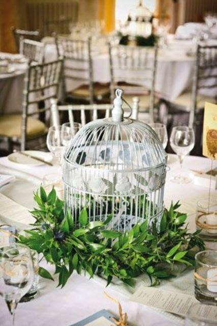 einen Vogelkäfig, umgeben von üppigem grün elegante und nicht-typische Hochzeit Herzstück