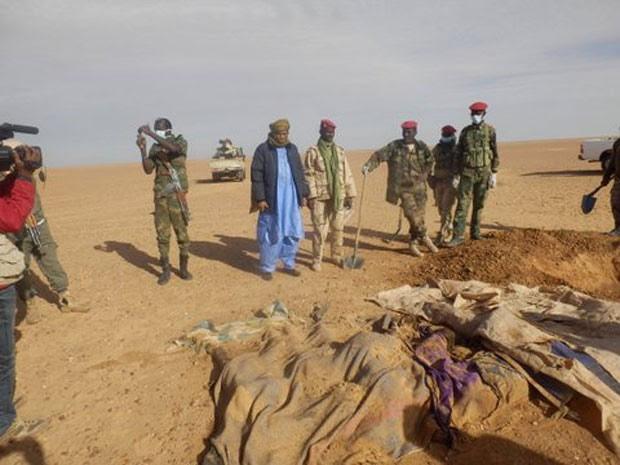Voluntários e militares observam os corpos retirados da areia do Saara, ao norte de Arlit, no Níger (Foto: Almoustapha Alhacen/AP)