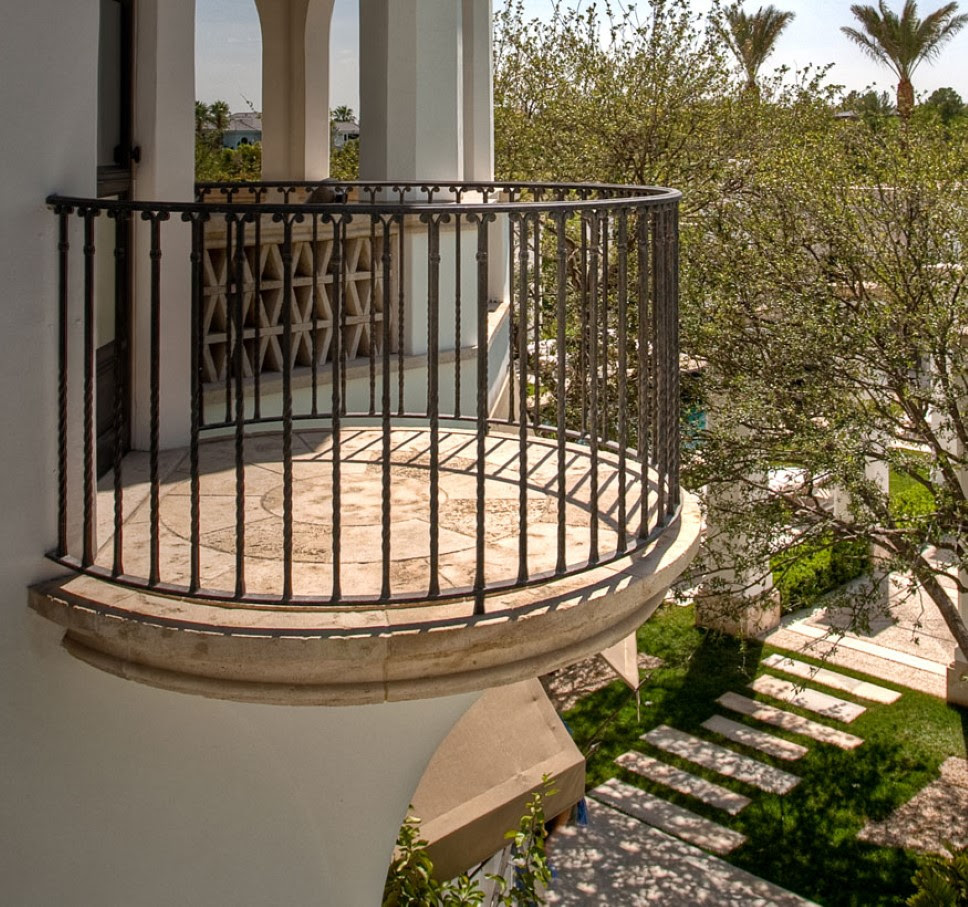 small round stone balcony design idea with iron femce and stone flooringa dn white siding and glass window and garden view