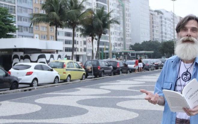 Eduardo Tornaghi exibe livro que vende nas ruas no calçadão da praia do Leme, no Rio de Janeiro - Rodrigo Anjos/Notícias da TV