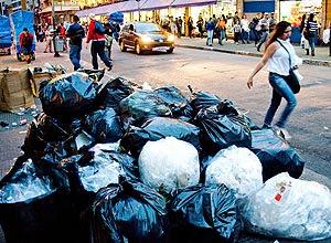 Rua 25 de Março, no centro de SP, tomada por sujeira deixada nas calçadas e na via pelos lojistas
