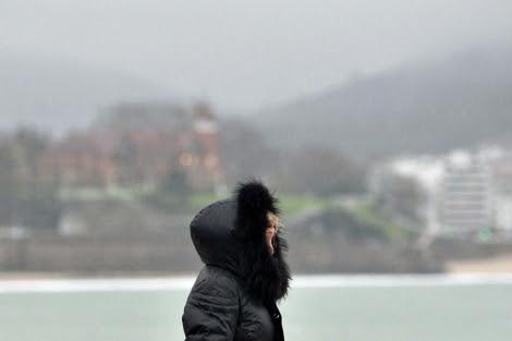 Una mujer se protege del frío y la lluvia en San Sebastián. | Efe