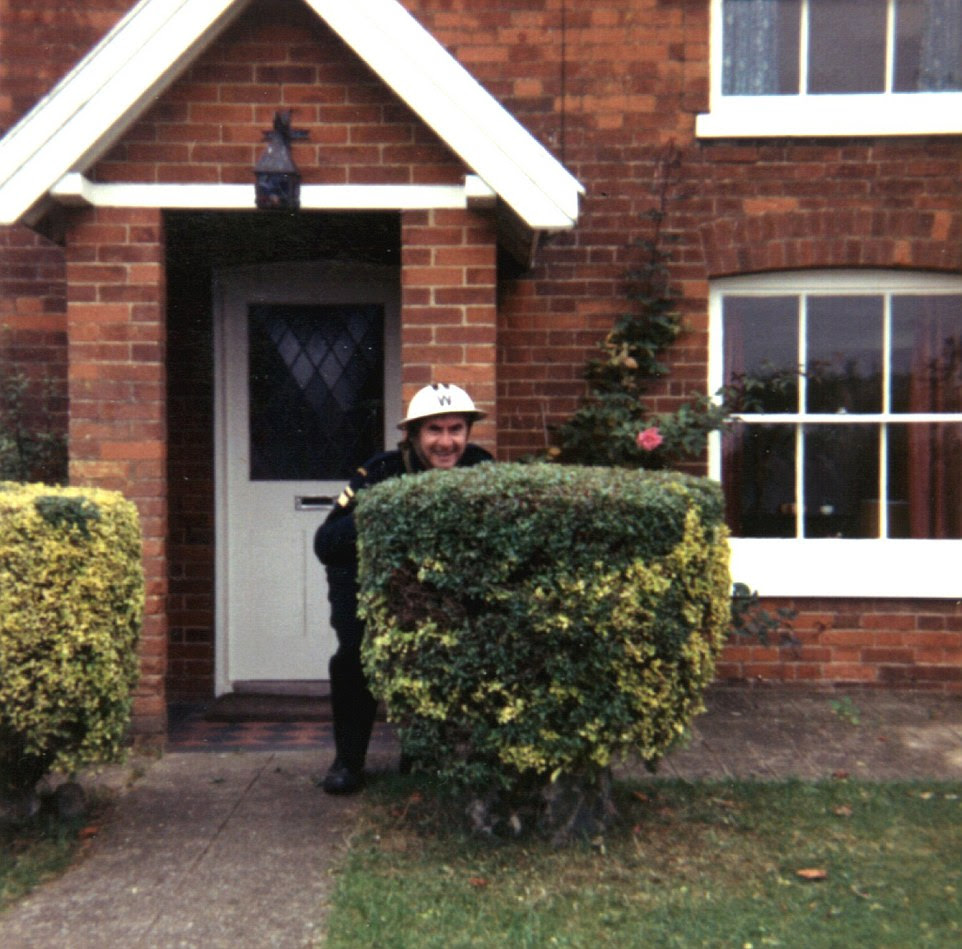 Expert camouflage: Bill Pertwee, dressed as Chief Warden Hodges, plays around on set during filming in Wacton. The crew used Rosalyn Barrett's house (pictured) for filming, and while she was only paid £10, Mr Pertwee agreed to take her and her husband out for dinner