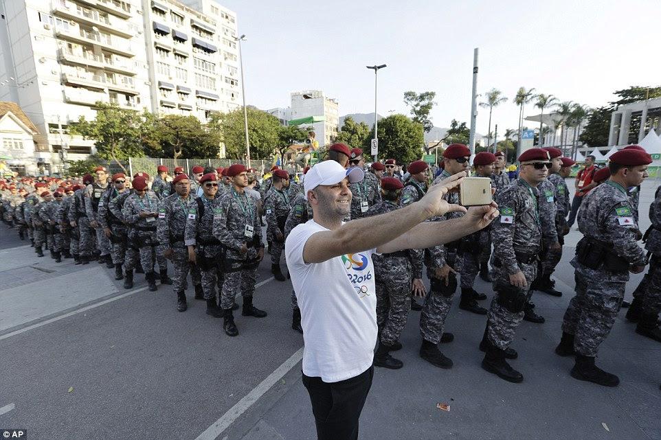 Estou com eles: Um fã de esportes furtivamente um selfie como colunas de soldados brasileiros montavam guarda fora do estádio do Maracanã