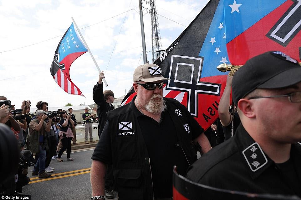 Un hombre vestido con la insignia de la Liga del Sur (centro) se une a la marcha NSM hacia Greenville Street Park