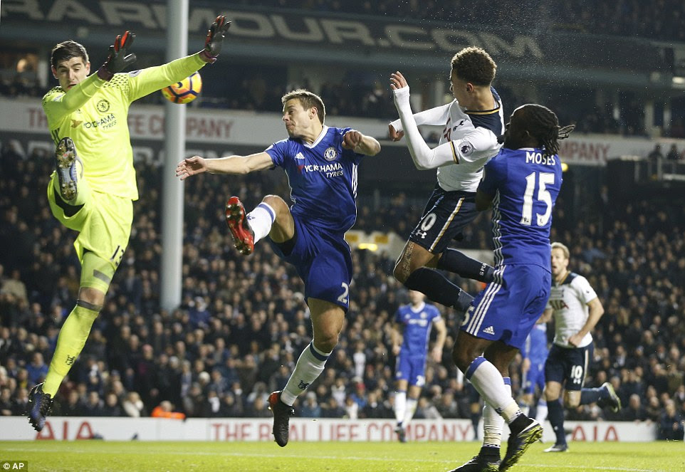 Chelsea's Belgian goalkeeper Courtois looks to spread his body but can't prevent Alli from doubling Tottenham's lead