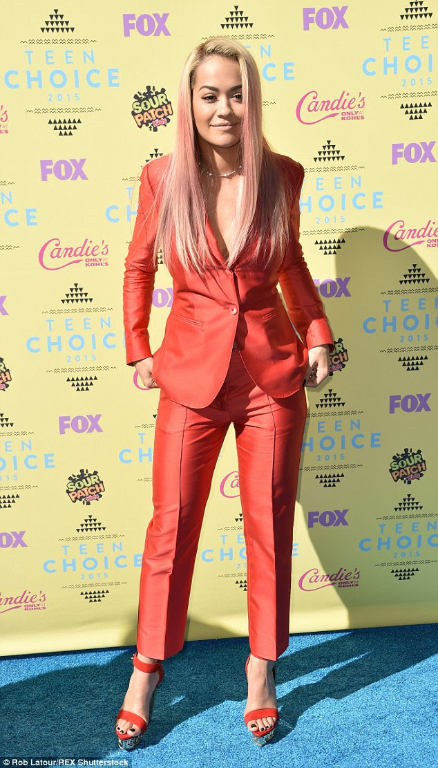 Smart suit: Rita donned a red blazer and matching trousers, paired with coordinating skyscraper heels