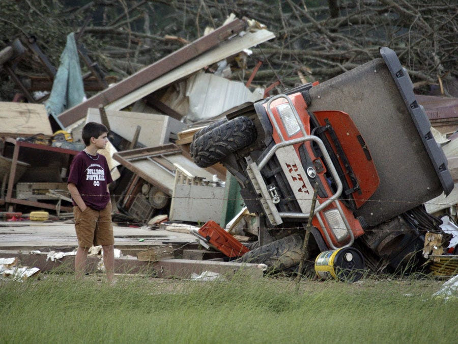 A boy looks at a destroyed home in Bond, Miss.