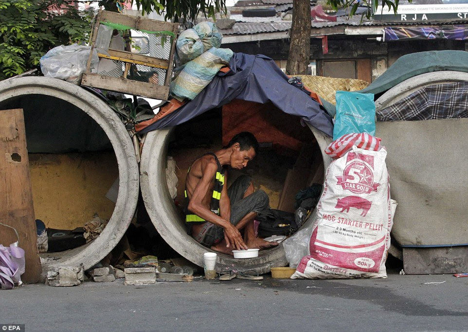 Cramped conditions: A Filipino informal settler rests inside a small sewer pipe with a few of his possessions behind him