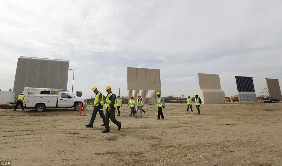 People pass border wall prototypes as they stand near the border with Tijuana, Mexico, on October 19