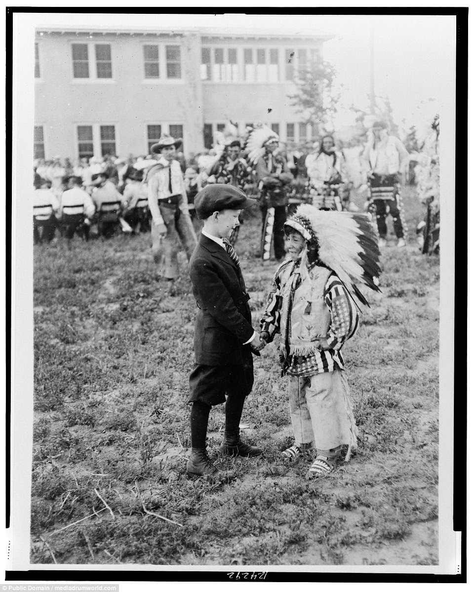 A white boy and and a Native American boy, wearing headdress, shaking hands, in 1923