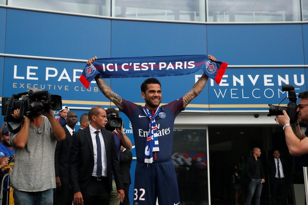 Uniformizado, Daniel Alves exibe o cachecol para a torcida do lado de fora do Parc des Princes na apresentação ao Paris Saint-Germain (Foto: REUTERS/Gonzalo Fuentes)