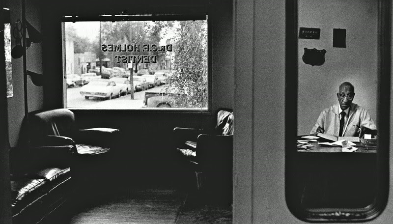 Description of  OCT 1 1970 - Dr. Clarence F. Holmes is reflected in a mirror at his desk. (John G. White/The Denver Post)