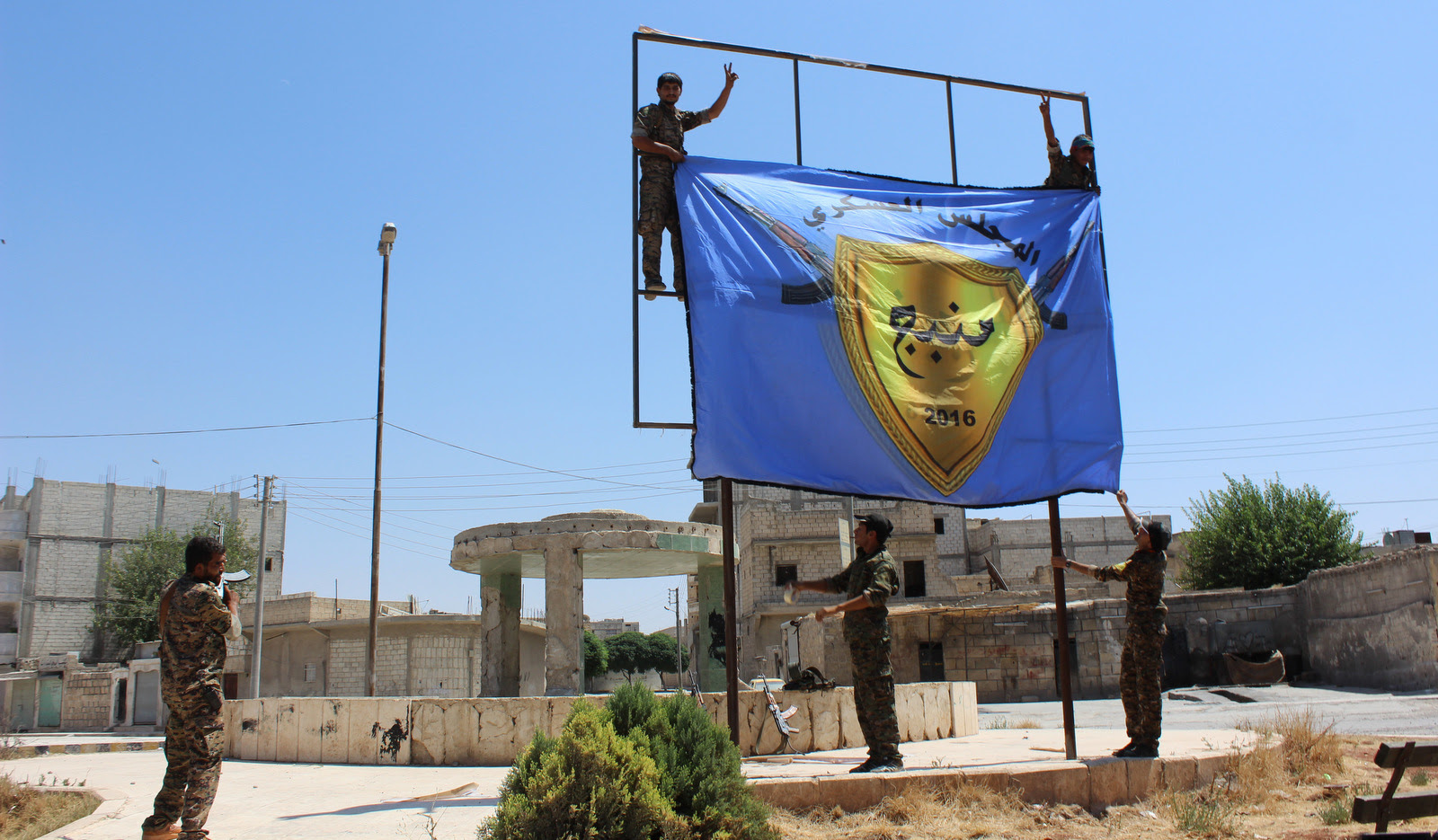 U.S.-backed, Kurdish-led Syria Democratic Forces raise their flag in the center of the town of Manbij after driving ISIS out of the area, in Aleppo province, Syria. (ANHA via AP)
