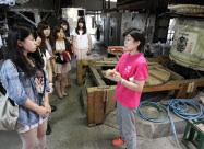 酒造会社の杜氏(右)の仕事を取材する跡見学園女子大の学生(9月、福島県会津若松市)
