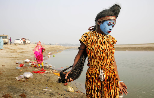 young Indian boy dressed as Hindu God Shiva walks the banks of the River Ganges looking for alms from devotees on the first day of the nine-day Navratri festival, in Allahabad, India,Tuesday, Oct. 13, 2015.  Navaratri lasts for nine days, with three days each devoted to the worship of  the goddess of valor Durga, the goddess of wealth Lakshmi, and the goddess of knowledge Saraswati. (AP Photo/Rajesh Kumar Singh)