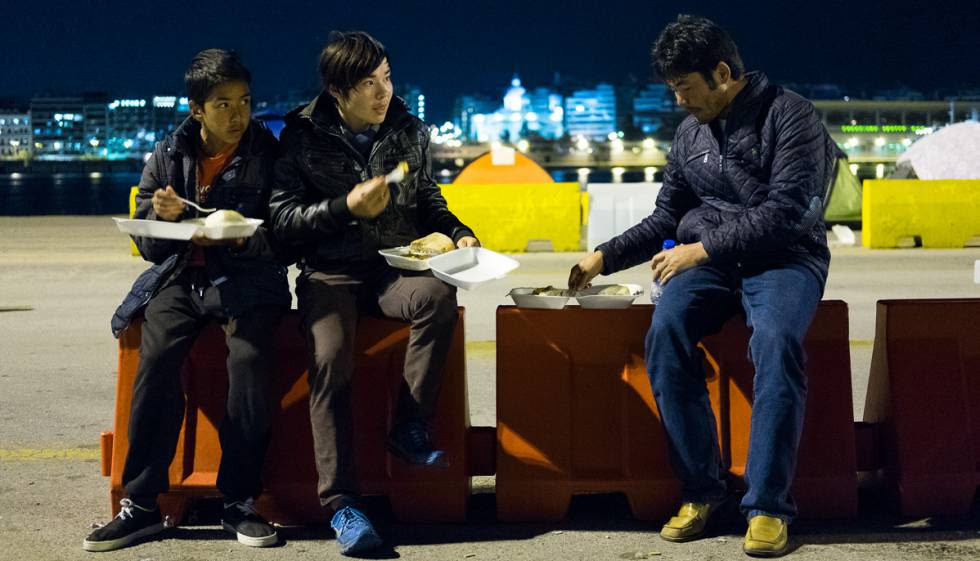 Tres jóvenes cenan las raciones que se distribuyen a los refugiados en el Puerto del Pireo, Atenas.