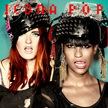 The two members of the group Icona Pop are photographed with their mouths open. They are both wearing large helmets which have been decorated with various items such as metal studs and feathers